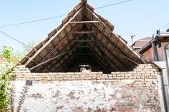 Casa abandonada e danificada velha com telhas de telhado e a parede branca com emplastro rachado no fundo do tijolo Imagens de Stock Royalty Free