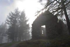 Casa abandonada en el bosque en un día de niebla Foto de archivo libre de regalías