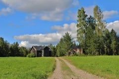 Casa abandonada en el camino de la grava Imagen de archivo libre de regalías
