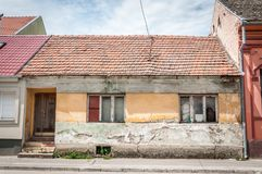 Casa abandonada velha com as janelas quebradas e danificadas na cidade arruinada pela idade imagem de stock