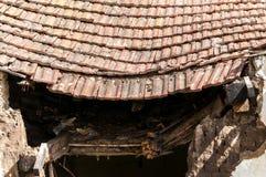 A casa abandonada velha desmoronou telhado com as telhas danificadas do vintage após a catástrofe natural do terremoto ou do fura Fotografia de Stock