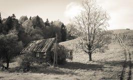 Casa abandonada vieja de la granja debajo de la colina imagen de archivo