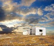 Casa abbandonata bianca sotto i cieli drammatici di tramonto Immagini Stock Libere da Diritti