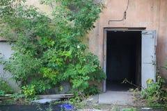 Casa abbandonata con la porta aperta Immagini Stock