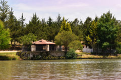 Casa abbandonata nella foresta, sull'orlo di un lago Immagini Stock Libere da Diritti