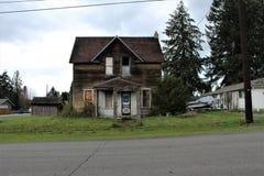Casa abbandonata nelle cadute del granito, WA & x28; view& anteriore x29; con un arco concreto nell'iarda anteriore fotografia stock