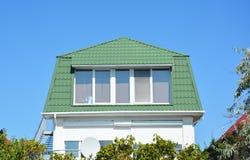 Casa acolhedor com sala bonita da mansarda do sótão, as janelas grandes, e o telhado verde do metal Imagens de Stock Royalty Free