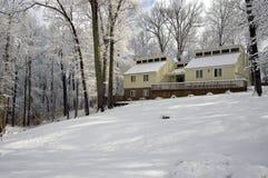 A casa acolhedor na neve cobriu o monte Imagem de Stock