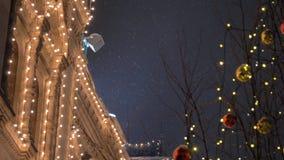 Casa adornada con la guirnalda y las bolas en árboles en una noche festiva en las nevadas almacen de video
