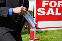 Casa: Agente Puts Brochures no tubo do sinal Fotos de Stock