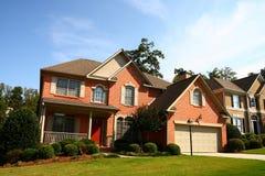 Casa agradável do tijolo com porta vermelha fotografia de stock royalty free
