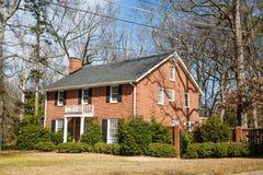 Casa agradável do tijolo no gramado do inverno Fotografia de Stock Royalty Free