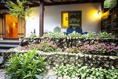 Casa agradable con la flor hermosa delante de ella Imagen de archivo libre de regalías