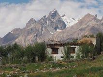 Casa agricola dell'alta montagna in mezzo dei campi verdi, alla parte posteriore dei picchi ripidi con i ghiacciai da completare, Fotografia Stock Libera da Diritti