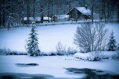 Casa alpina dello Snowy e fiume congelato nel legno Fotografia Stock