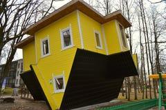 A casa amarela encontra-se no telhado, a casa é girada, foto de stock