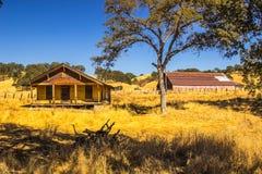 Casa amarilla abandonada vieja de la granja con el granero grande en Gackground Foto de archivo libre de regalías