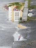 Casa amarilla con la bandera americana reflejada en charco Foto de archivo