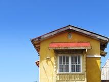 Casa amarilla en el cielo azul Fotografía de archivo