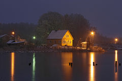 Casa amarilla en el lago congelado en la noche Fotografía de archivo libre de regalías