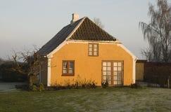 Casa amarilla en la puesta del sol Imagenes de archivo