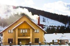 Casa amarilla grande con una chimenea que fuma Foto de archivo