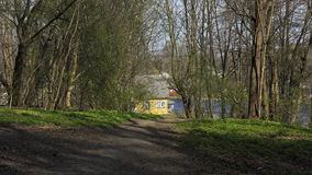 Casa amarilla por la opinión del lago del parque Foto de archivo