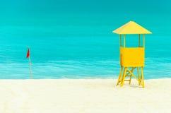 Casa amarilla y bandera roja en la playa Imagenes de archivo
