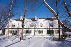 Casa ancestral larga del francés-estilo blanco hermoso con los obturadores y la puerta de granero verdes imágenes de archivo libres de regalías