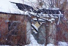 Casa arruinada marrón vieja del ladrillo con las ventanas negras vacías en la nieve blanca demasiado grande para su edad con las  imagenes de archivo