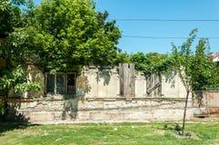 Casa arruinada velha com telhado desmoronado e as janelas quebradas cobertos com a placa de madeira fotografia de stock