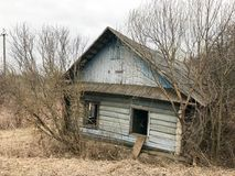 Casa azul arruinada abandonada de madeira dilapidada velha azul velha da vila dos feixes com janelas quebradas Imagens de Stock Royalty Free