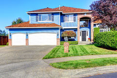 Casa azul clara exterior con el ajuste del ladrillo y el tejado de teja Foto de archivo