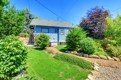 Casa azul pequena com o jardim no pátio traseiro. imagens de stock