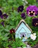 A casa azul pequena no canteiro de flores com viola floresce Imagens de Stock