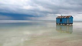 Casa azul vieja abandonada en el medio del lago de sal durante una tormenta inminente Salar Baskunchak almacen de metraje de vídeo