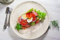 Casa, bacon, salsicha, ovo e verdes secundários do sanduíche em um baguette, placa, vista superior, ainda vida Imagens de Stock