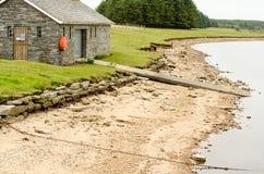 Casa barco y embarcadero al lado de la playa y del lago imagenes de archivo