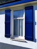 Casa bianca d'annata con l'otturatore della finestra e il curta blu aperti del pizzo Immagini Stock
