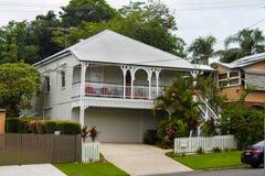 Casa bianca del queenslander con pianta tropicale ed alberi alti il giorno nuvoloso in Australia Fotografie Stock Libere da Diritti