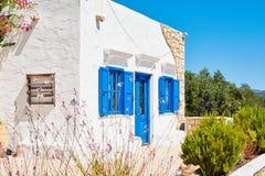 Casa bianca dell'argilla con le finestre blu luminose e una porta Immagini Stock Libere da Diritti