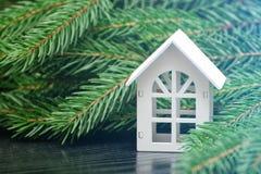 Casa bianca su un fondo di un ramo verde dell'abete Immagini Stock Libere da Diritti