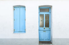 Casa blanca con los obturadores y la puerta azules Fotos de archivo