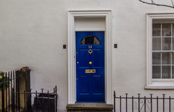 Casa blanca con una puerta azul con un golpeador de cobre amarillo Foto de archivo libre de regalías
