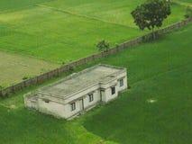 casa blanca en centro del campo verde Imagenes de archivo