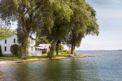 Casa blanca en una línea de la playa sombreada del lago fotografía de archivo libre de regalías