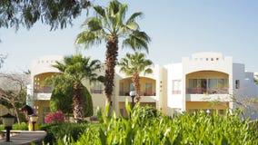 Casa blanca moderna de lujo que pasa por alto un jardín ajardinado tropical almacen de metraje de vídeo