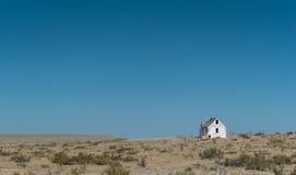 Casa Blanca vieja abandonada en los llanos debajo de un cielo azul Imágenes de archivo libres de regalías