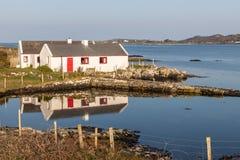 Casa blanca y roja alrededor de la bah?a de Clifden imagen de archivo