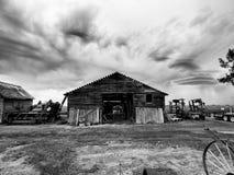 Casa blanco y negro del almacenamiento de la granja, con el fondo vivo de los cielos de la lluvia: Imagen de archivo libre de regalías